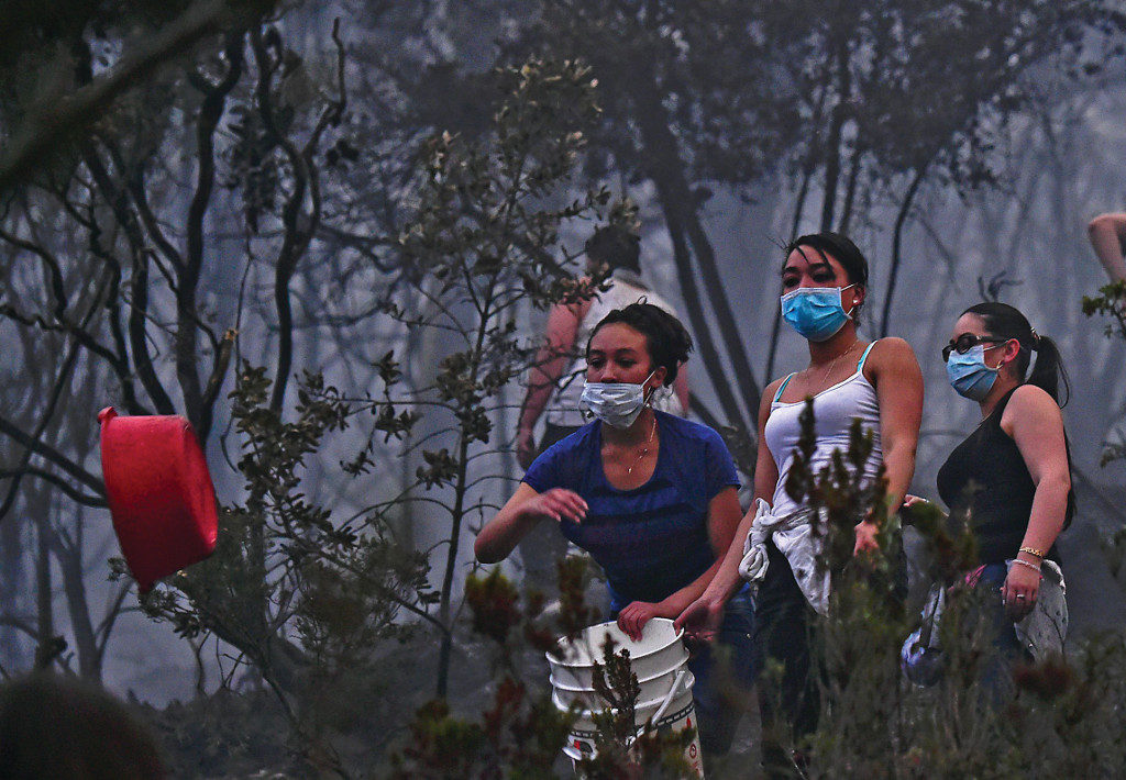 People try to put out a forest fire in Bogota, in February 2, 2016. A yellow alert was declared Tuesday in Bogota due to the air pollution caused by a forest fire near the capital's downtown, where government buildings, schools and other entities were evacuated, authorities reported. AFP PHOTO/ Luis ACOSTA / AFP / LUIS ACOSTA (Photo credit should read LUIS ACOSTA/AFP/Getty Images)
