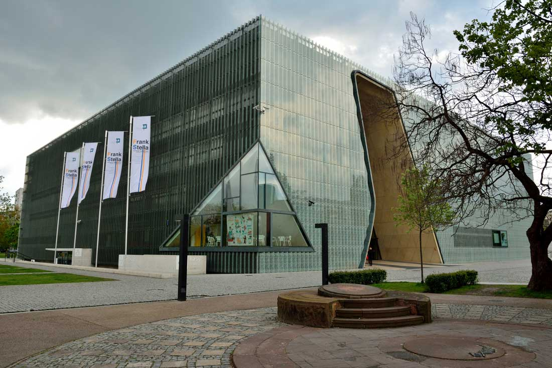 Exterior view of the Museum of History of Polish Jews, in Warsaw, with Ghetto Heroes Monument and people.