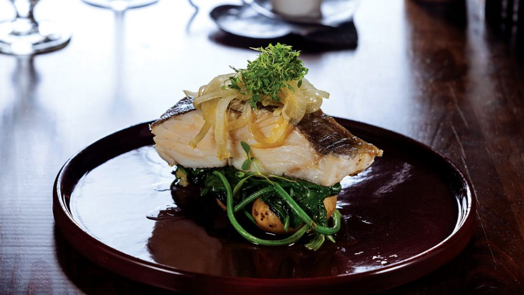 Cod Fish steak confit in olive oil with greens and potatoes/Traditional Portuguese cuisine