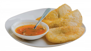 A plate with empanadas and sauce