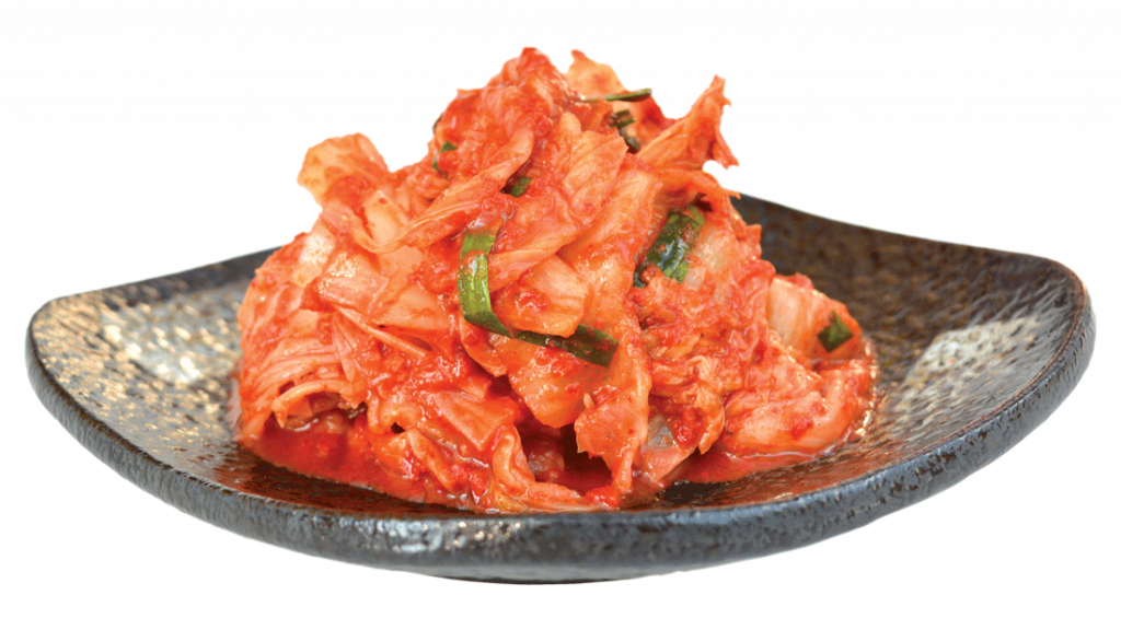 Kimchi on black plate, isolated on white background
