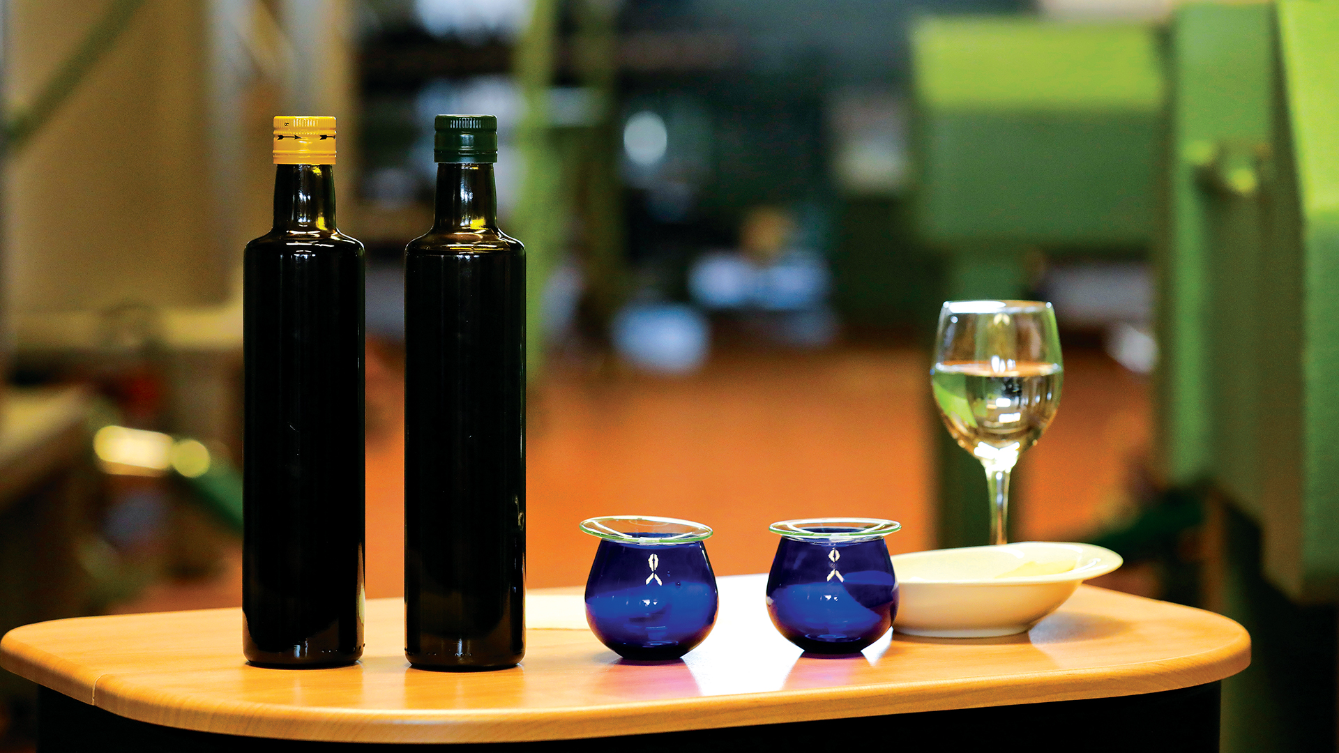 Table with olive oil bottles, glasses, a glass of water and apple slices