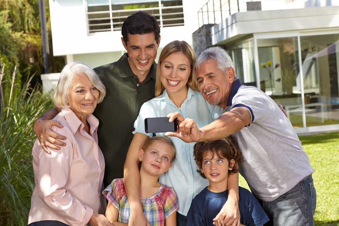 Selfie of family in three generations with children in summer in front of a house