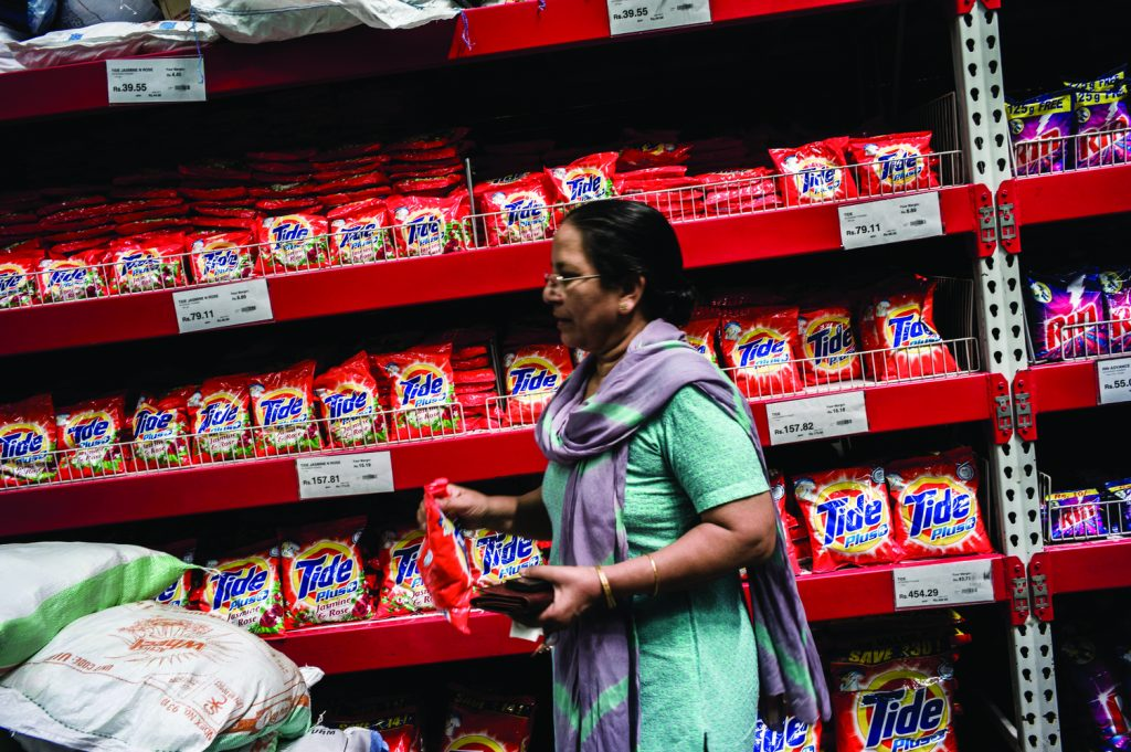 A shopper takes a bag of Procter & Gamble Co. Tide detergent off the shelves of a Bharti Walmart Pvt. Ltd.