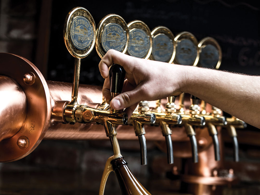 a hand choosing and serving one of various types of beer