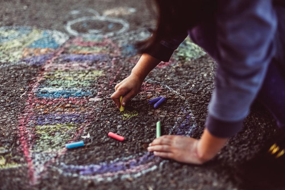 Little girl chalk drawing on asphalt