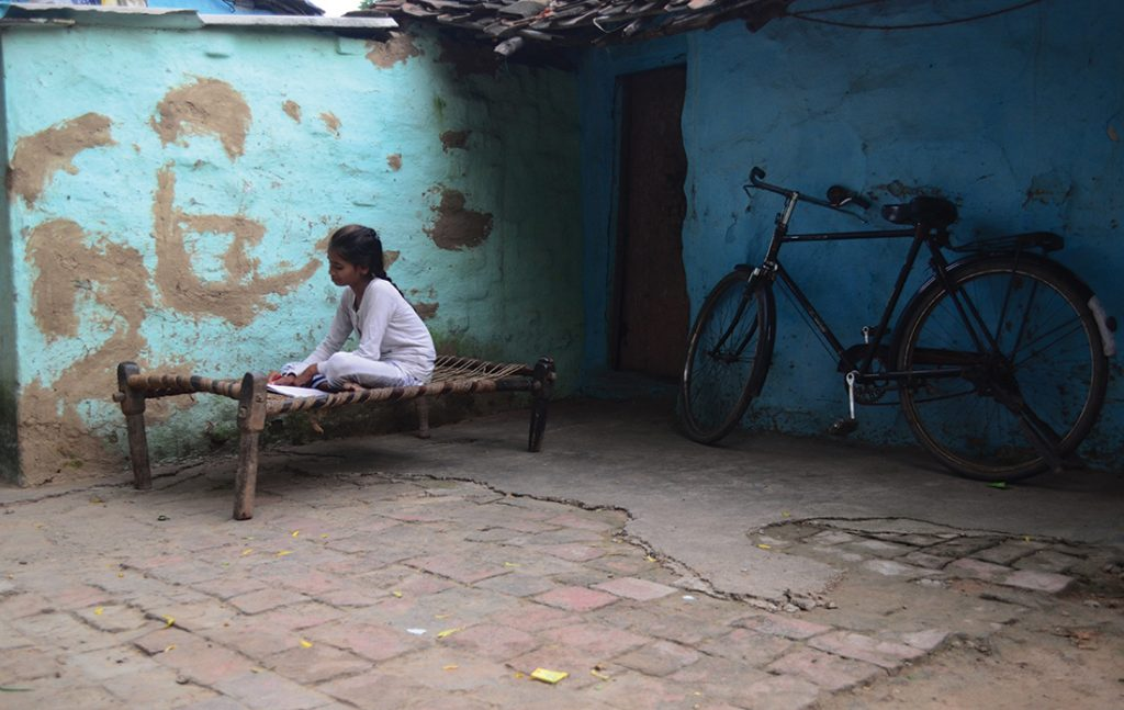 An Indian girl studies outside her house in slums on World Literacy Day , in Allahabad on September 8,2016.