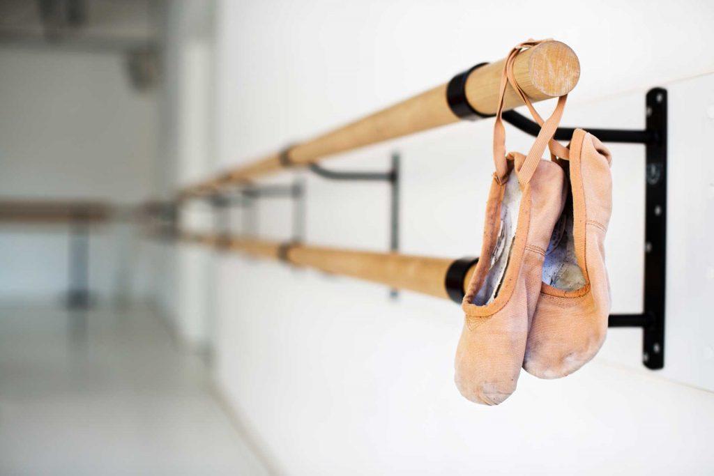 Ballet shoes hanging on wooden barre in studio