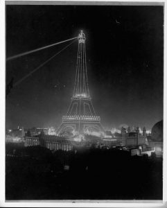 Spotlights illuminate the Eiffel Tower at night during the 1900 Exposition.
