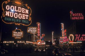 View of the illuminated sign of casinos and hotels along Fremont Street, Las Vegas, Nevada, 1955. Visible are signs for the Golden Nugget, the Lucky Strike Club, the Pioneer Club, the Las Vegas Club, the Boulder Club, and the Hotel Apache, among others.