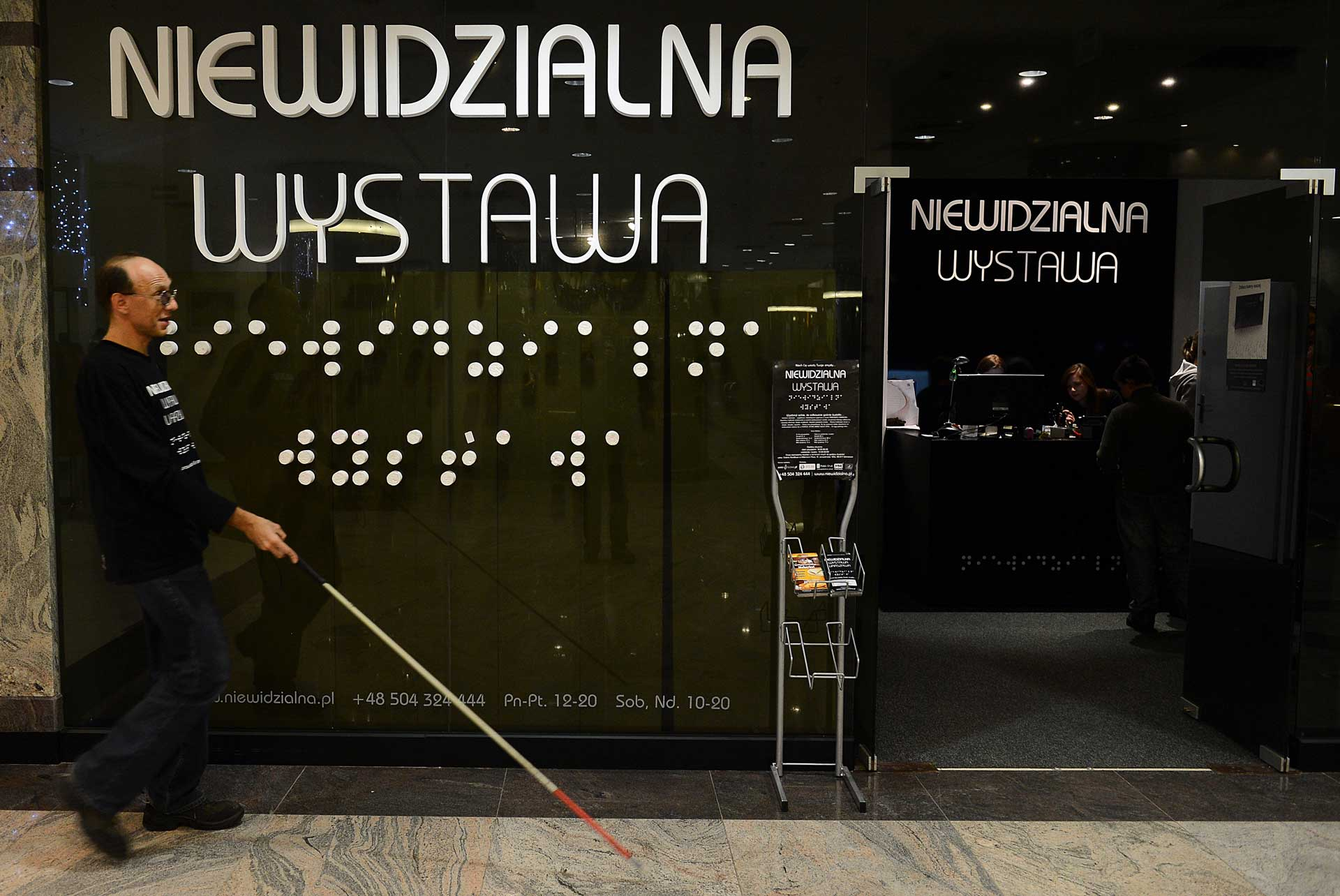 A blind guide walks past the entrance to the 'invisible exhibition' on December 18, 2012 in Warsaw.