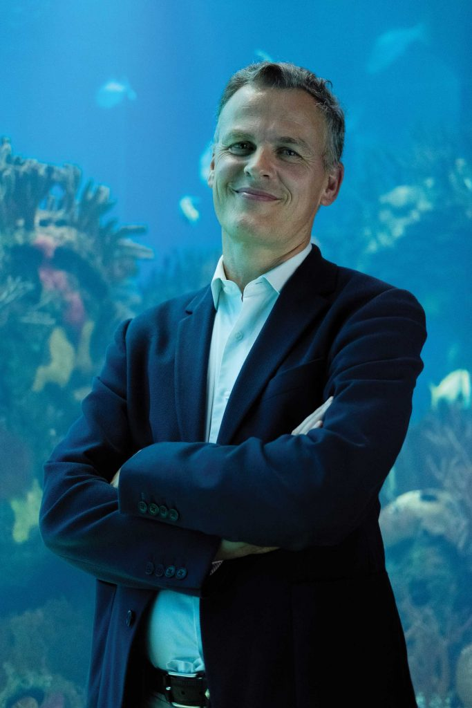 Photography of João Falcato in front of big aquarium of Oceanário