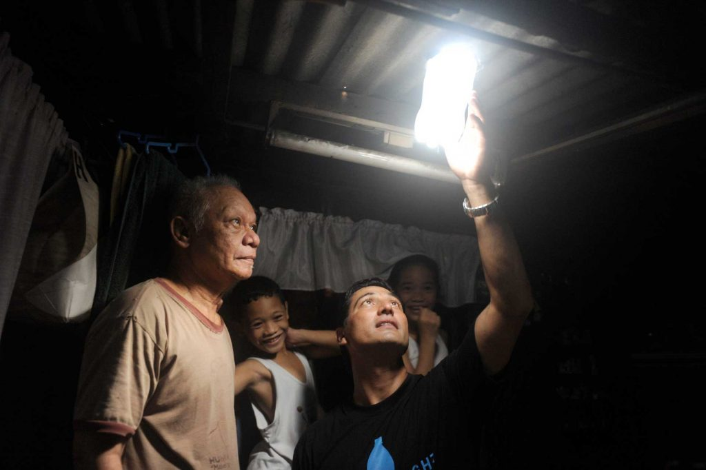 Karl Malakunas Illac Diaz inspect a solar light bulb with Siplicio Mondas, 73, and his grand son.