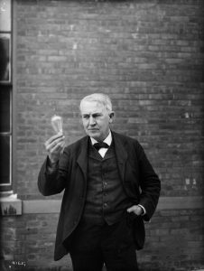 Inventor and physicist Thomas Alva Edison looking at a lightbulb