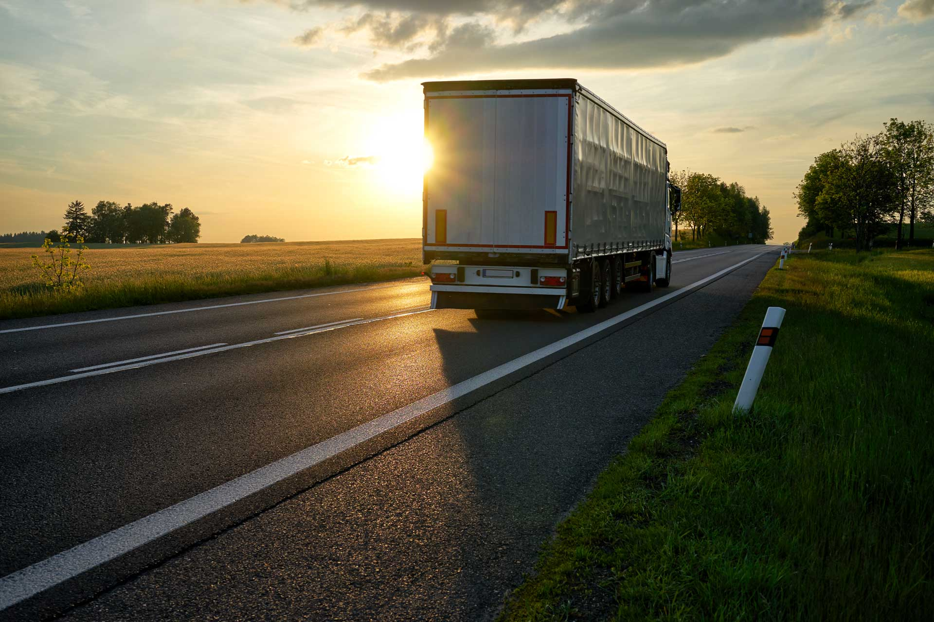 """Truck departing towards the horizon on an asphalt road in a rural countryside at sunset. """