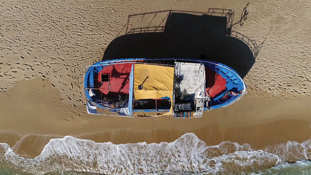 Aerial top down photo of beach and stranded refugee boat at southern mediterranean beach showing the colorful vessel located at the yellow beach with human footprints also showing the azure blue ocean