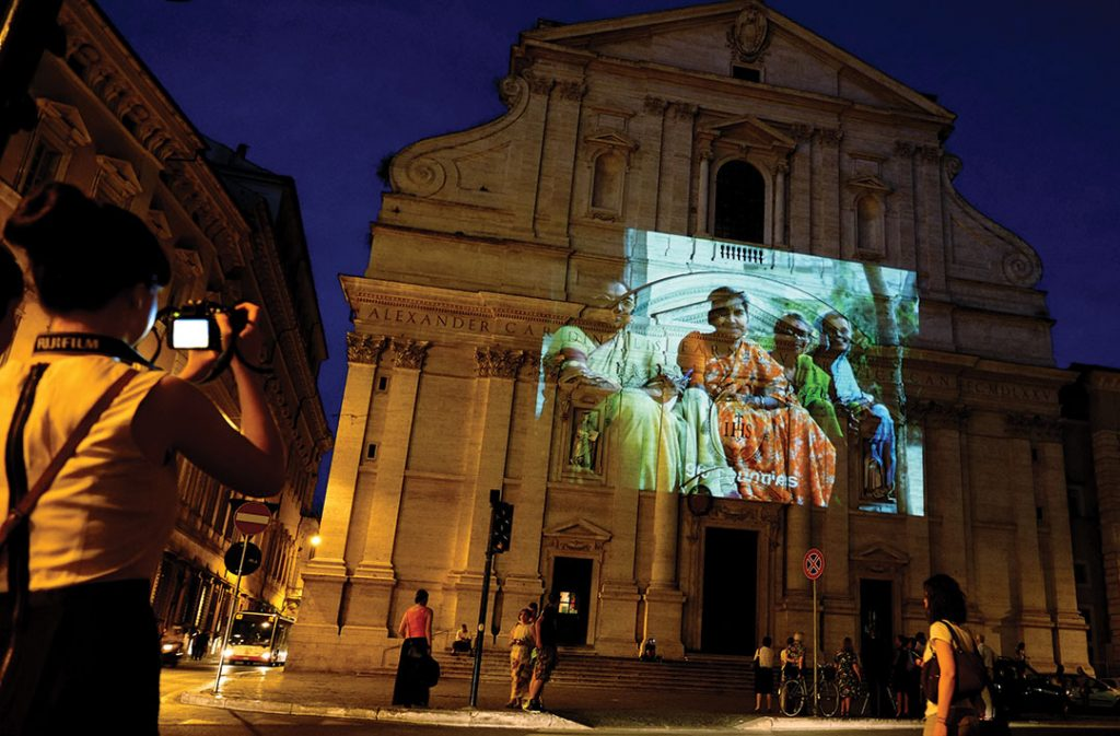 An outdoor digital photo projection is seen on the facade of the church of Jesus in Rome on June 18, 2013. The Jesuit Refugee Service is launching an awareness campaign through 200 photographs projected in a 12-minute video.