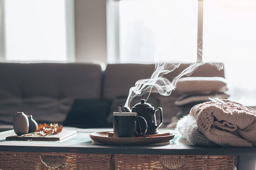 Still life details in home interior of living room. Sweaters and cup of tea with steam on a serving tray on a coffee table.