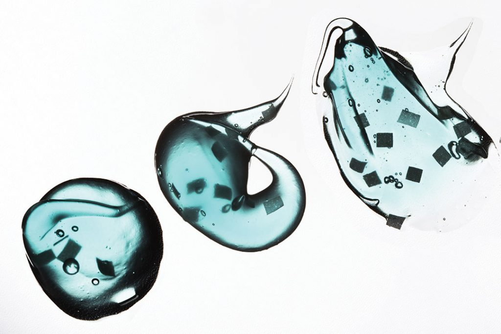 Smear paint of cosmetic products on a white background, micro beads particles in blue transparent toothpaste
