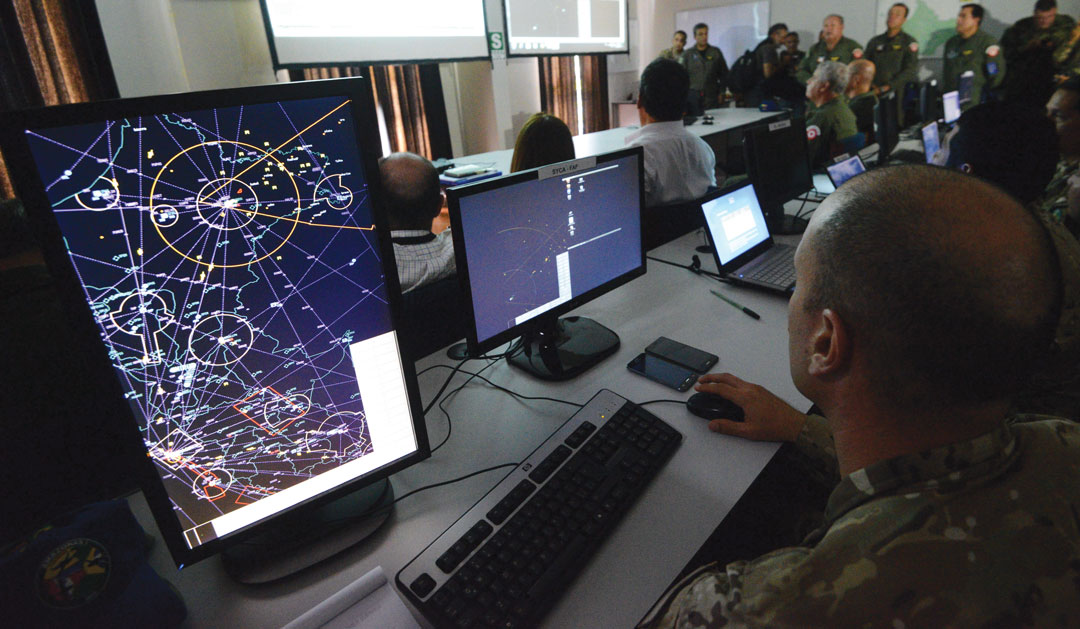 Members of a tri-national Air Force team of Brazil, Colombia and Peru watch from a control center the joint exercises designed to improve tactics and strategies to fight drug smuggling in their air borders in Iquitos