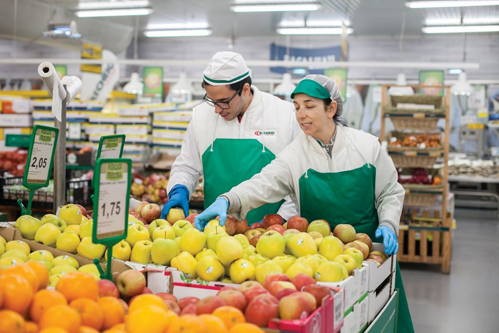 man and woman working near the fruits at supermarket