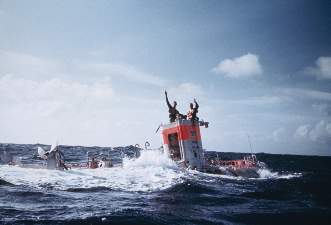 Explorers wave victoriously from a bathyscaph after a seven-mile dive, Marianna Trench, Pacific Ocean, near Guam