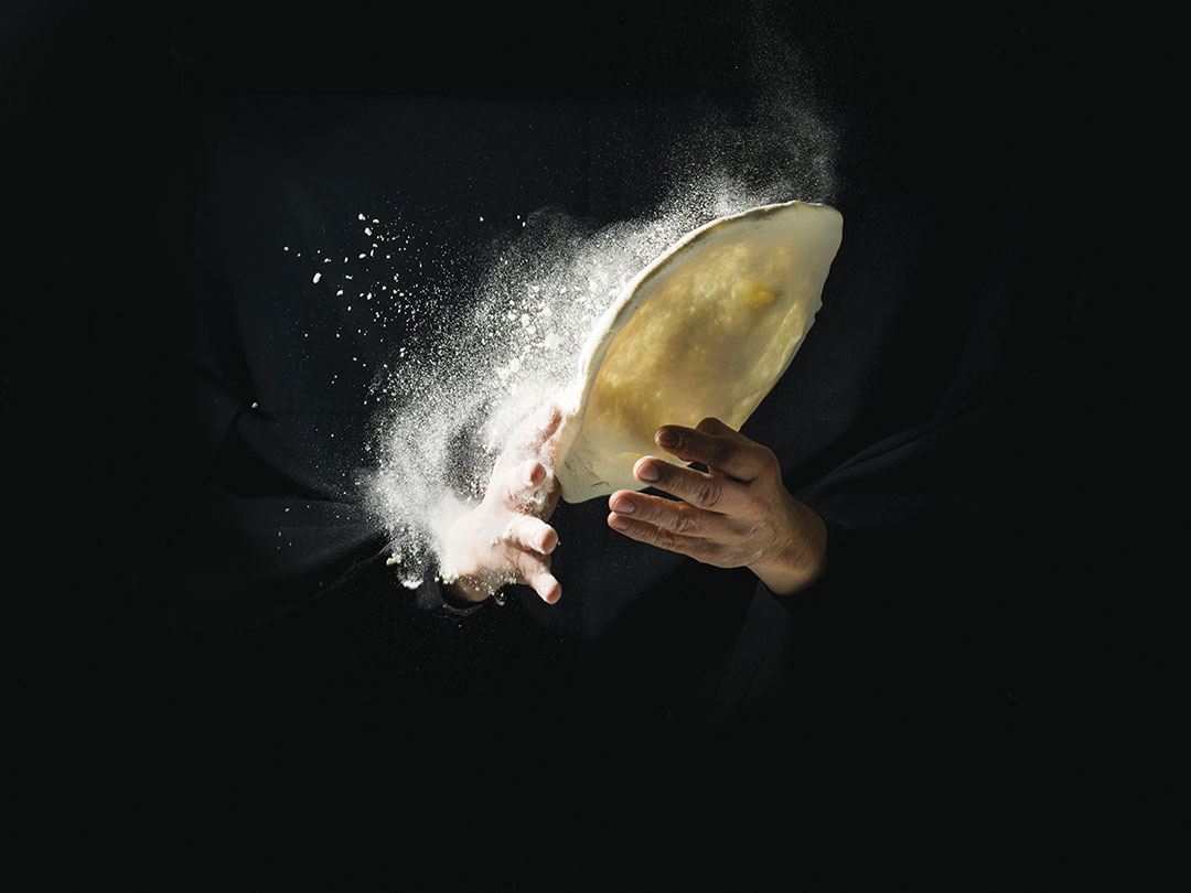 Fliying pizza dough with flour, on drak background