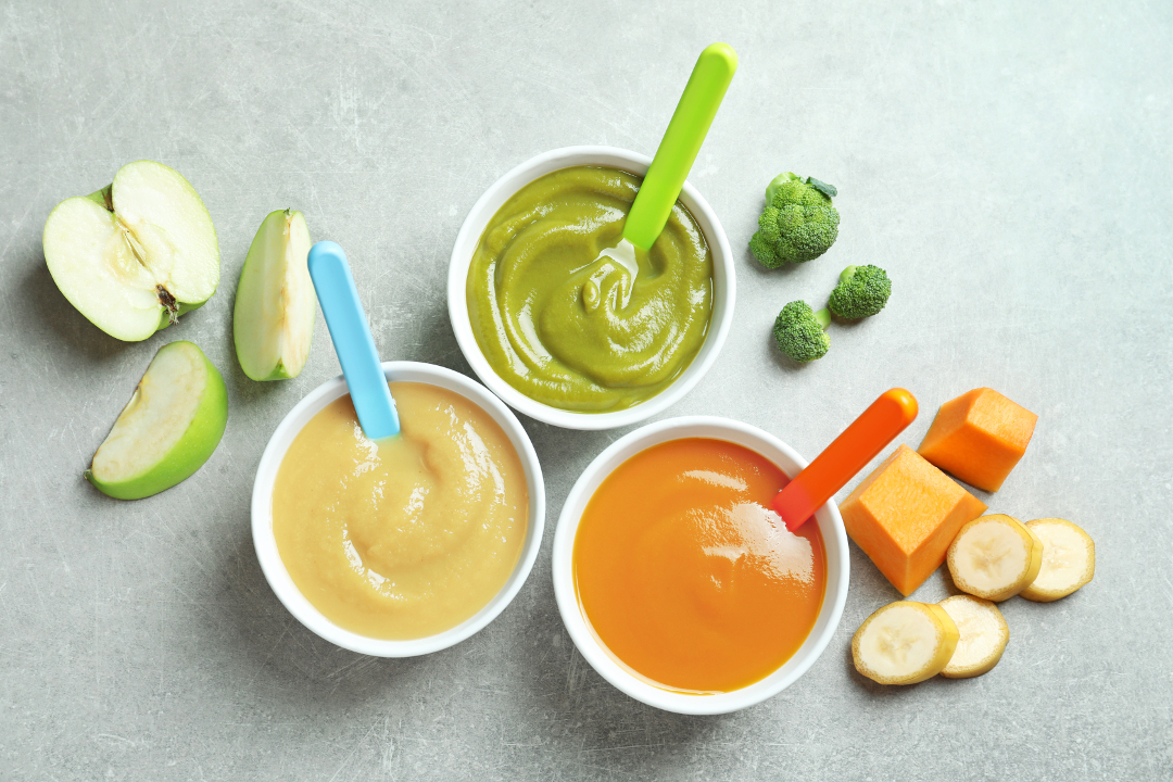 bowls with baby's food on grey background