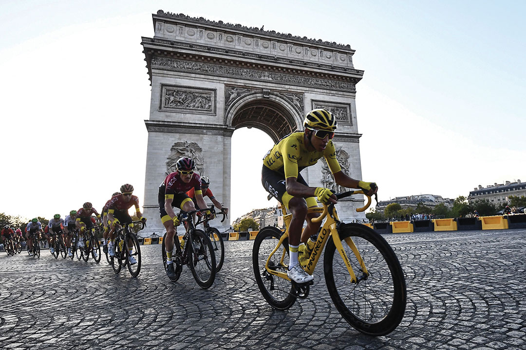 Colombia's Egan Bernal (R), wearing the overall leader's yellow jersey (C-R) and cyclists ride down the Champs Elysees avenue next to the Arc de Triomphe during the 21st and last stage of the 106th edition of the Tour de France cycling race between Rambouillet and Paris Champs-Elysees, in Paris, on July 28, 2019.