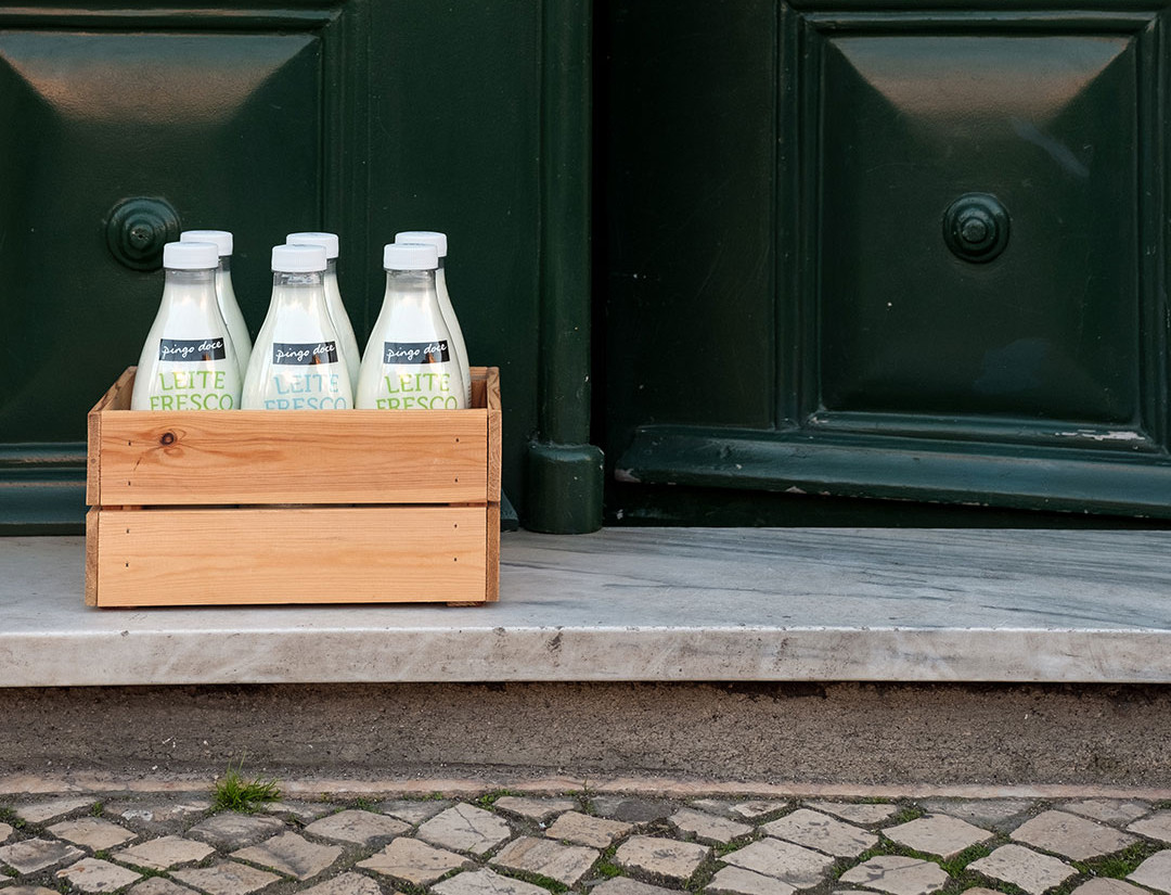 Basket full of fresh milk bottles, in front of a door.