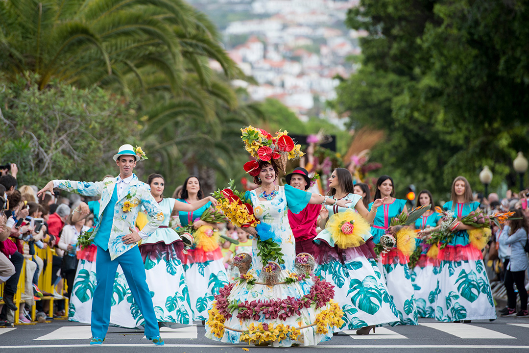 people dressed in colorful clothes at the Festa da Flor in city of Funchal on the island of Madeira.