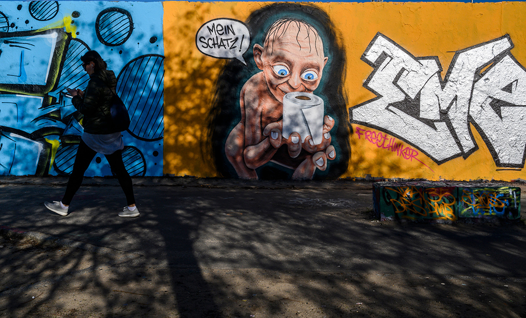 "A woman walks past a mural painting by graffiti artist Eme Freethinker depicting a likeness of the Gollum/Smeagol of the ""Lord of the Rings"" epic, worhsipping a toilet paper roll with a speech bubble reading ""My darling"", at Berlin's Mauer Park on March 21, 2020, amidst the new coronavirus COVID-19 pandemic."