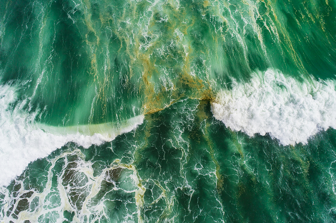 Aerial view of waves splashing in sea.