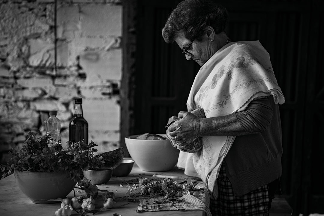 Black and white photography of Adelina Maria José, preparing a traditional dish, called Açorda