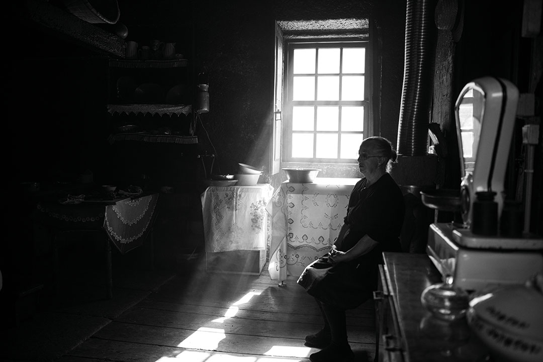 Black and white photography of an old woman in her house