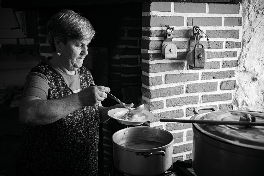 Black and white photography of a woman, Maria Laura, serving soup