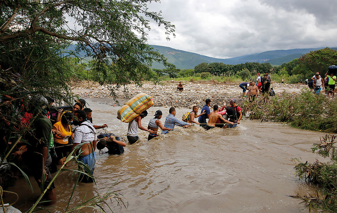 Migrants use a rope to cross the Tachira river, the natural border between Colombia and Venezuela, as the official border remains closed due to the COVID-19 pandemic in Cucuta, Colombia, on November 19, 2020.