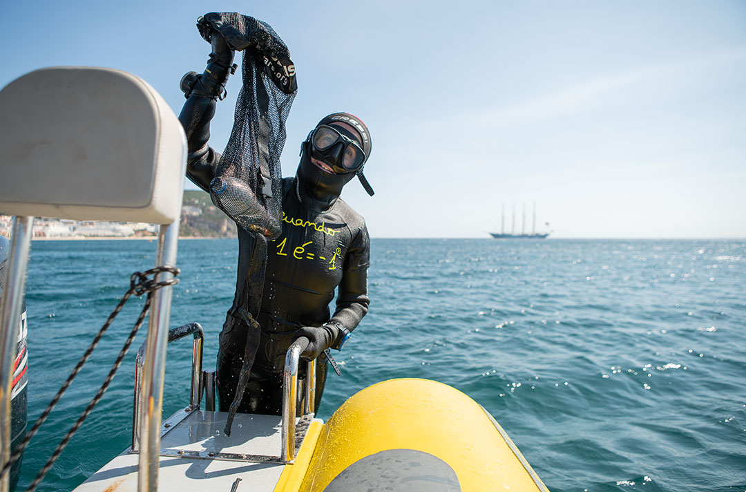 Scuba diver volunteer holding a plastic bottle collected from the ocean